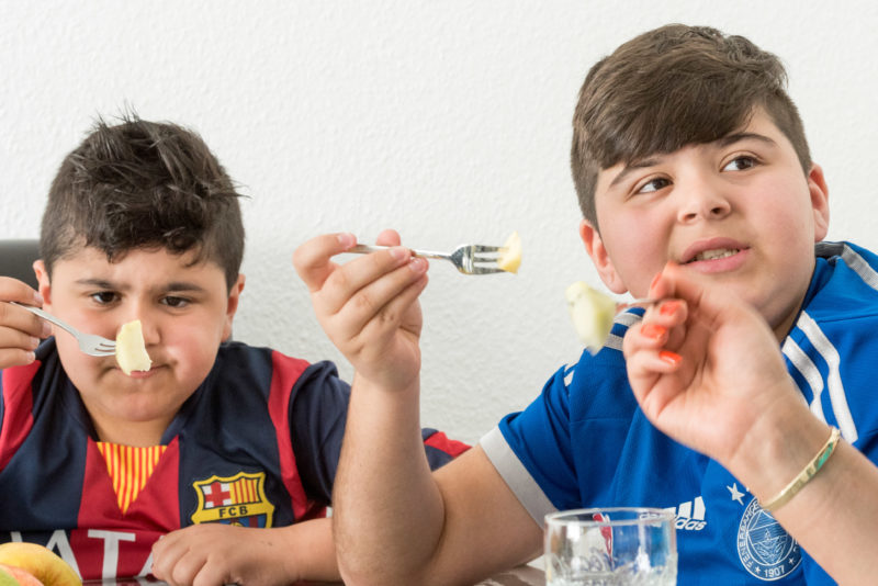 Editorial photography, subject learning and education: Two younger brothers while eating fruit at home at the family table.