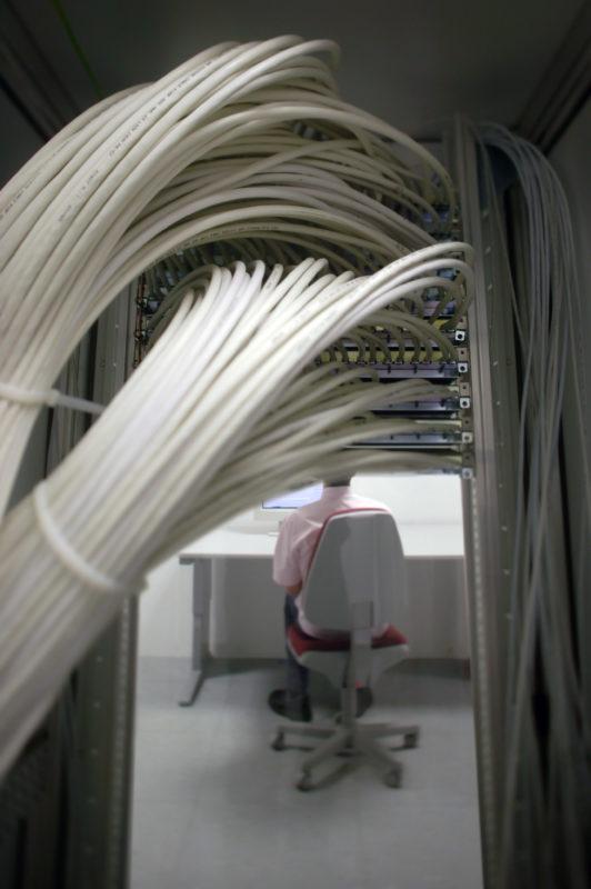 Industriefotografie: Ein Computernutzer in einem Rechenzentrum sitzt an seinem Bildschirm hinter ihm laufen dutzende Kabel in einem Rack zusammen.