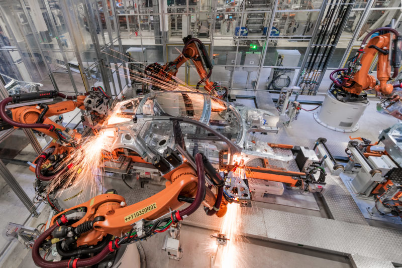 Industrial photography: Welding robots are working on a vehicle body in a large automobile factory.