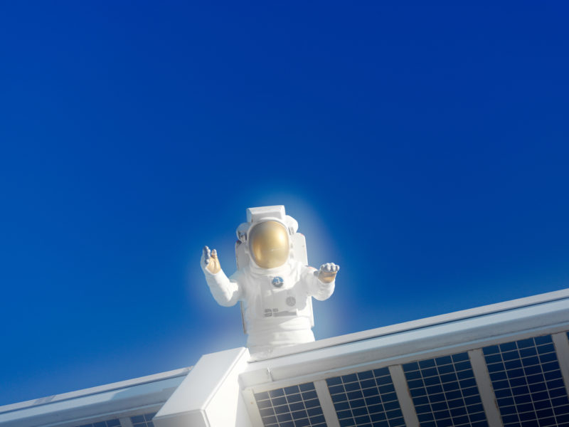 editorial photography: The doll of an astronaut is above the entrance to the Kennedy Space Center in the blue sky.