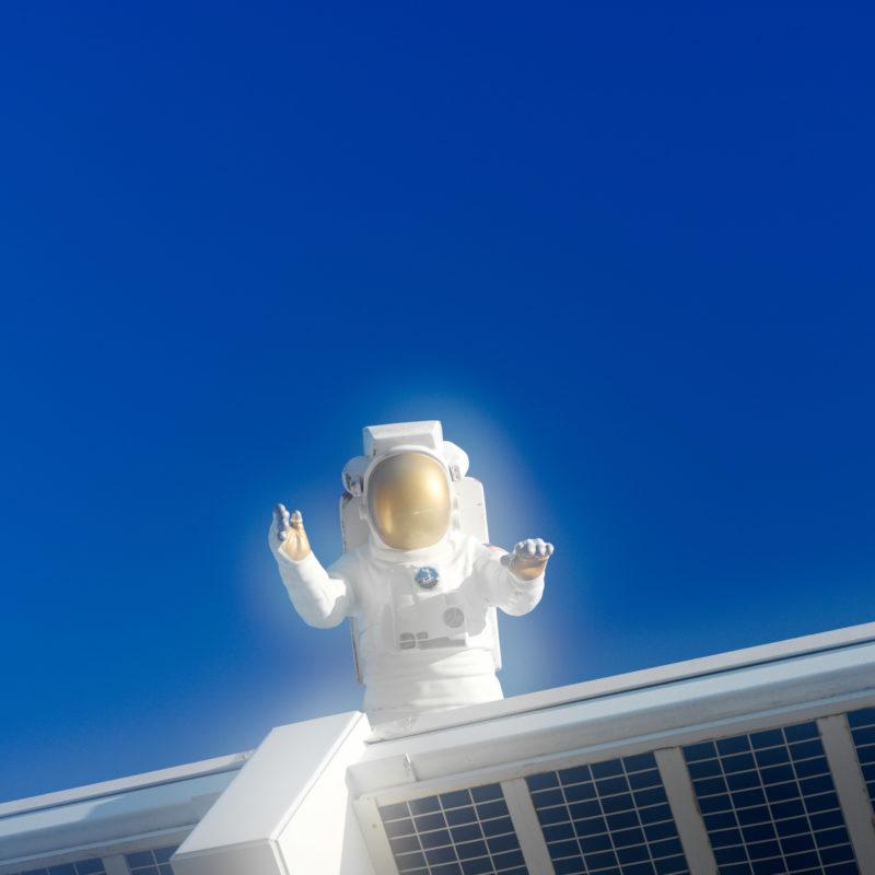 Luftaufnahmen und Drohnenfotografie: Reportagefotografie: Die Puppe eines Astronauten ragt über dem Eingang zum Kennedy-Space-Center in den blauen Himmel.