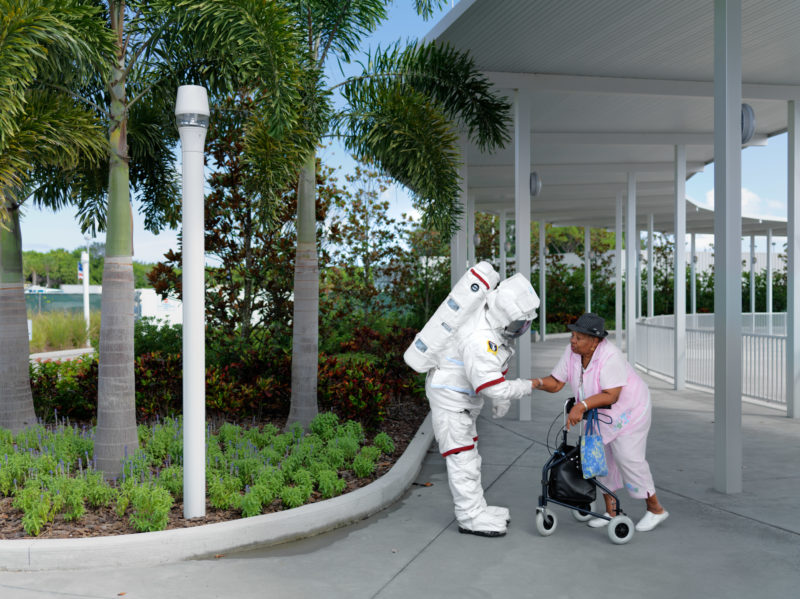 editorial photography: A Costumed astronaut welcomes an elderly woman in the visitor area.
