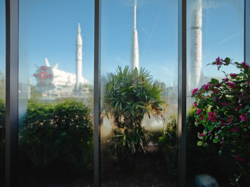 editorial photography: Through the window of a conference building you see disused rockets.