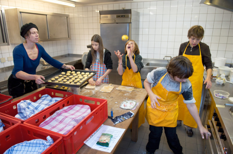 Editorial photography, subject learning and education: A school class at the cooking class under the supervision of a teacher at the Hohenlohe Open Air Museum. A student throws pastry dough in the air.