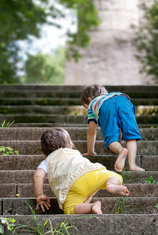 Editorial photography: As his older brother a small child attempts to climb a staircase.