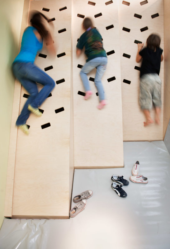 Editorial photography: Children climbing on a wooden climbing wall with grip and climbing holes. On the soft mat in front are the children