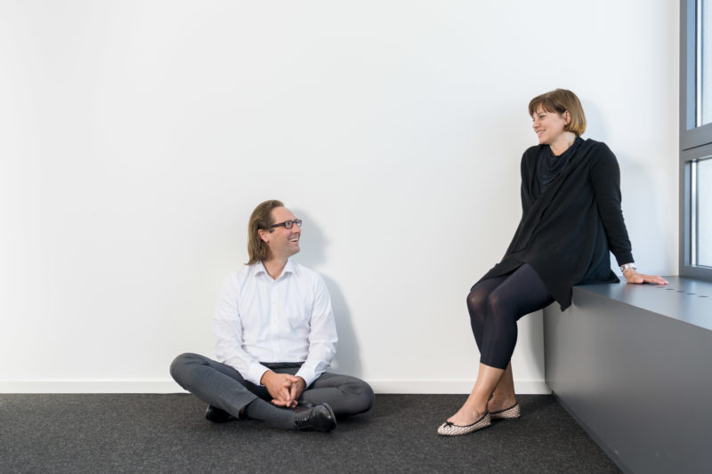 Employees photography: A man sits in an office room on the carpet while his colleague makes herself comfortable on a windowsill.