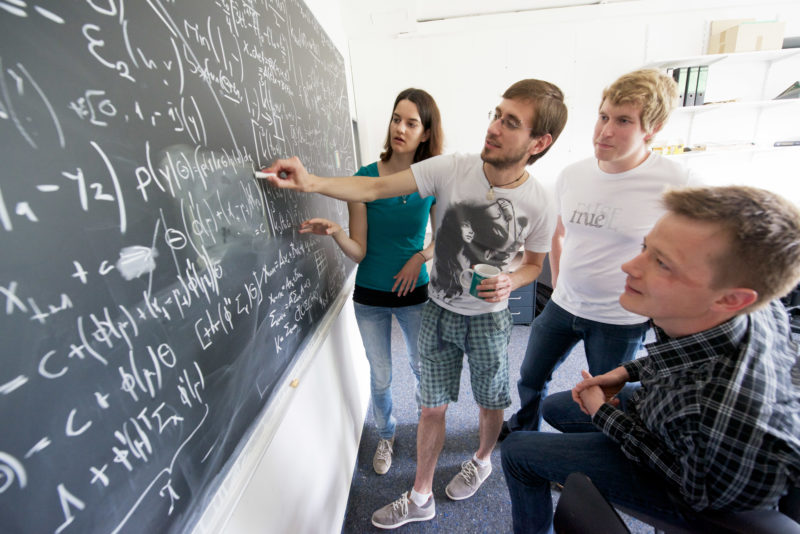 Science photography: Employees of the Max Planck Institute for Intelligent Systems talk in front of a blackboard full of mathematical formulas.