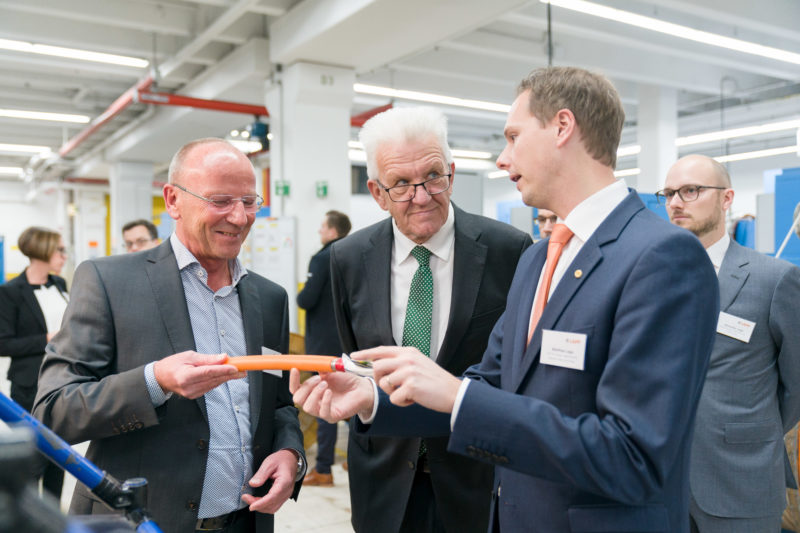 Editorial photography as event photography and fair photography: Winfried Kretschmann, Prime Minister of Baden-Württemberg, visits the company Lapp Kabel in Stuttgart and gets explained the construction of a special cable manufactured there.