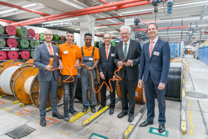 Event photography, editorial photography: Winfried Kretschmann, Prime Minister of Baden-Württemberg and company representative including two refugees who are training here.posing with an electric car charging cable in their hand while visiting the company Lapp Kabel in Stuttgart for a press photo.