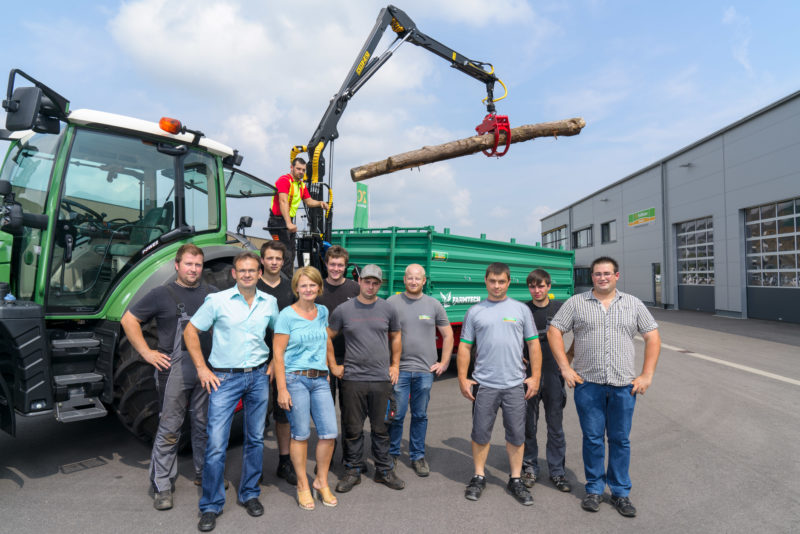Group photo: Employees of an agricultural machinery dealer in front of one of their offered products, a trailer to transport wood on a tractor. On the crane of the hanger hangs a tree trunk.