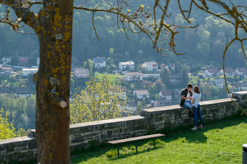 Landscape photogaphy: A teenage couple on a romantic viewpoint on a castle grounds above a typical small town in Germany with lots of summer greenery.