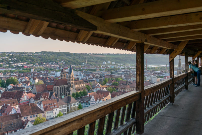 Landscape photogaphy: A couple looks from the castle above the vineyards to the city of Esslingen on the Neckar in the evening light.