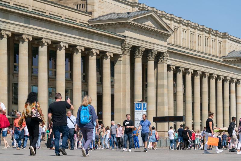 Stadtportrait Stuttgart: Landschaftsfotografie: Stadtansicht aus dem sommerlichen Stuttgart: Vor den Säulen des Königsbaus sind viele Fussgänger auf der Königsstraße unterwegs.
