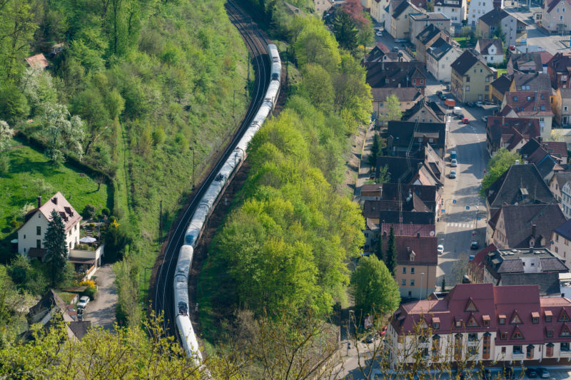 Landscape photogaphy: An Intercity Express winds its way through a valley. Green trees separate the railway line from the houses of a settlement.