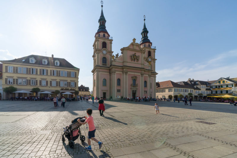 Landscape photogaphy: The market place of the Swabian city of Ludwigsburg with the baroque protestant city church. In the foreground a father with playing children.