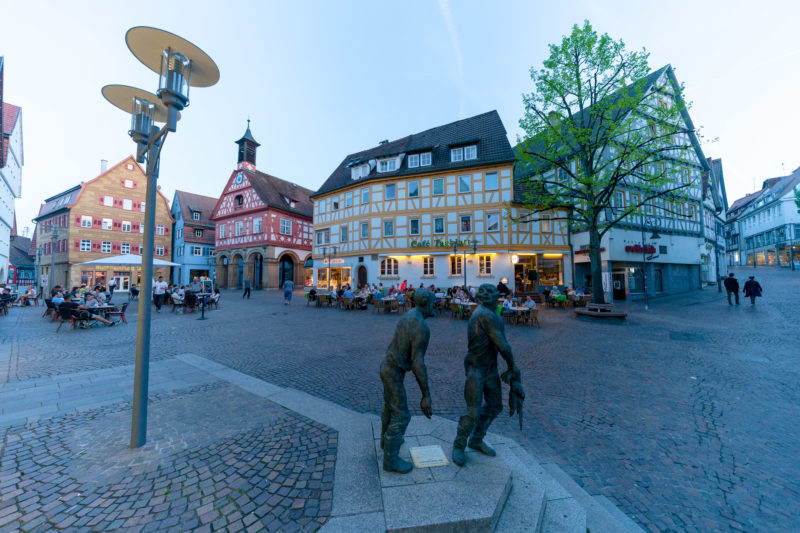 Landscape photogaphy: City view from the market place in Waiblingen. The photo was taken in the blue hour. Many guests are sitting in front of the Café Tagblatt. In the foreground the sculpture Die Taubenhäusler by the artist Karl-Henning Seemann.