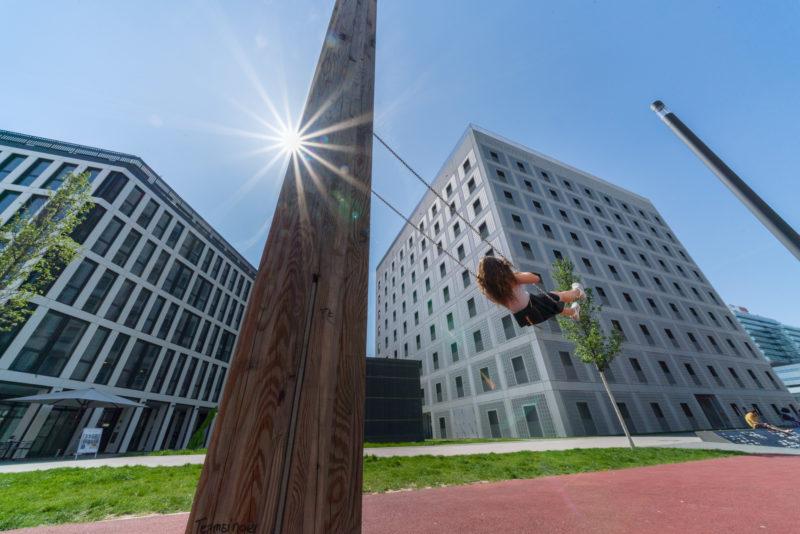 Stadtportrait Stuttgart: Landschaftsfotografie: Vor den modernen Gebäuden am Pariser Platz in Stuttgart schaukelt ein Kind in der Sonne.
