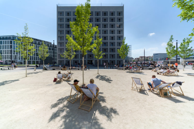 Landscape photogaphy:  On the sunlit Pariser Platz in Stuttgart, people sit in beach chairs. In the background, the striking building of the municipal library rises into the blue sky. Green young trees line the scene.