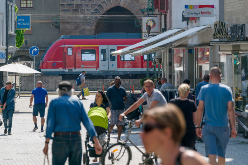 Landscape photogaphy: A typical urban scene with passers-by, far-riding bicyclists, a train and shops in a medium-sized German town.
