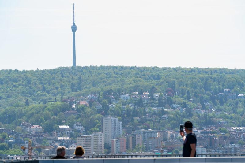 Stadtportrait Stuttgart: Landschaftsfotografie: Ein Blick über die Stadt Stuttgart. Man sieht die umliegenden bebauten aber grünen Hänge und darüber den Fernsehturm, eines der Wahrzeichen der Stadt. Im Vordergrund fotografiert ein Tourist ein Selfie.