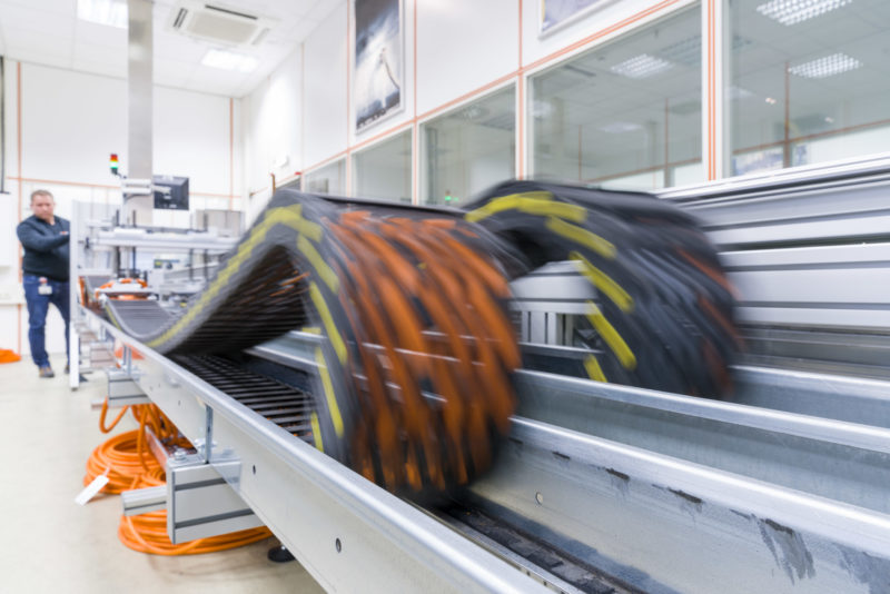 Industry photography: In a test laboratory: In the test centre of a cable manufacturer, cables are automatically moved back and forth hundreds of thousands of times in a cable chain guide in order to test long-term stability against cable breakage.