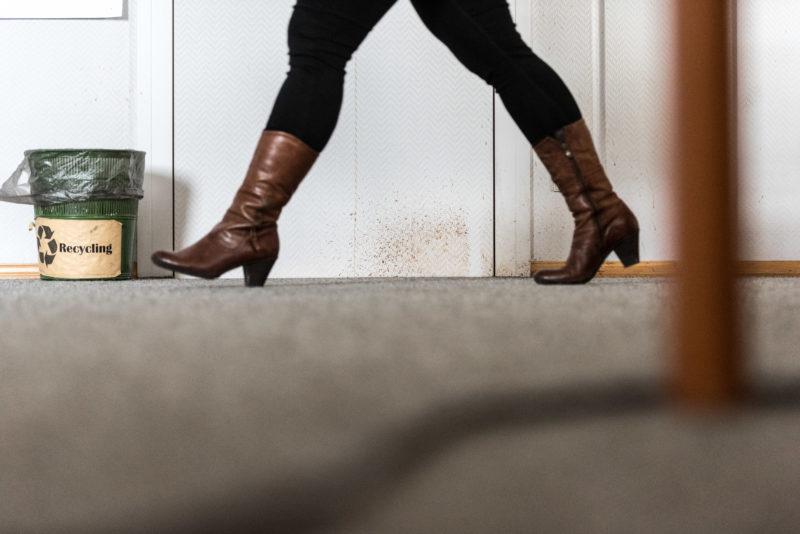 Im Vordergrund sieht man die Lederstiefel einer Frau, die mit großen Schritten an der schmutzigen Wand eines Büros entlang geht. Dahinter ein Abfalleimer mit einem vergilbten Recycling-Hinweis.