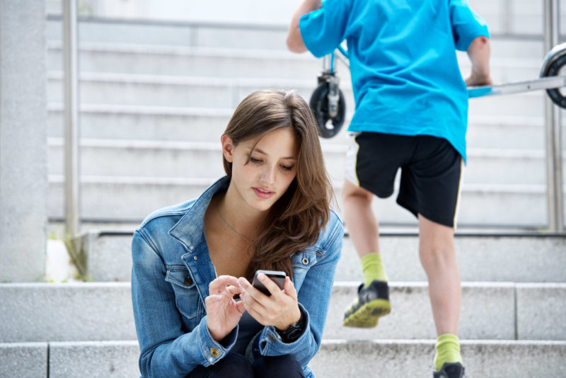 Lifestyle photography: A young woman is sitting outside on a staircase looking at her smartphone while a boy is running up the stairs in the background.
