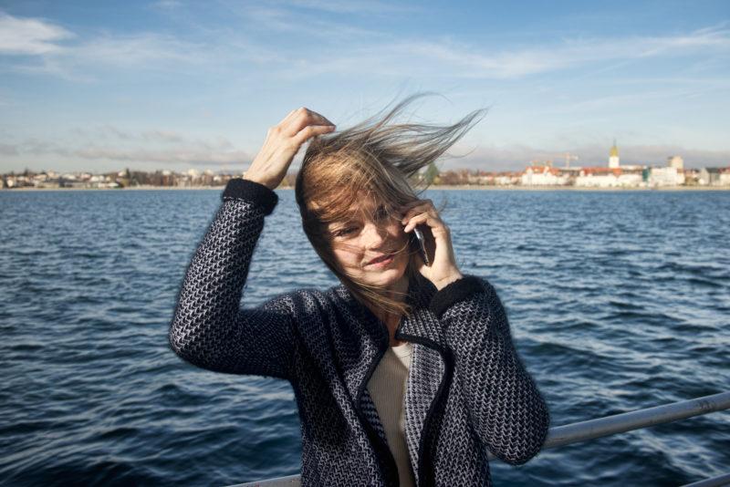 Lifestylefotografie: Eine Frau mit wehenden Haaren telefoniert mit dem Smartphone an Bord einer Fähre auf dem Bodensee. Ihre Haare wehen so sehr im Wind, dass man ihr Gesicht kaum sieht.