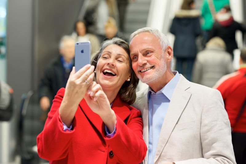 Selfie: Senior Couple in a mall makes a self portrait with their smartphone.