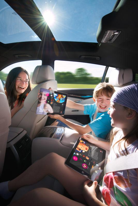 Industriefotografie: Lifestyle-Fotografie: Eine Familie im Auto auf einen Ausflug. Die Kinder surfen auf den Rücksitzen mit Tablet-Computern im Internet.