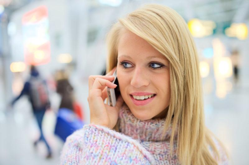 Lifestyle-Fotografie: An einem Flughafen telefoniert eine junge blonde Frau mit Ihrem Handy. Im Hintergrund gehen Reisende mit Koffern vorbei.
