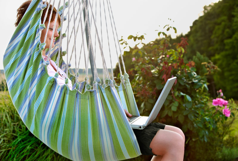 Lifestyle photography: A girl in a hammock surfs the Internet with her laptop.