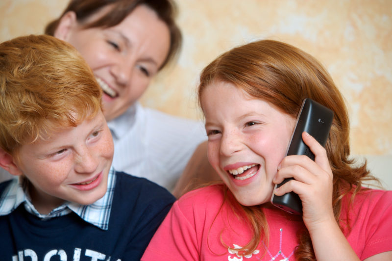 Lifestyle-Fotografie: Die Tochter telefoniert zuhause dabei ihr Bruder und ihre Mutter.
