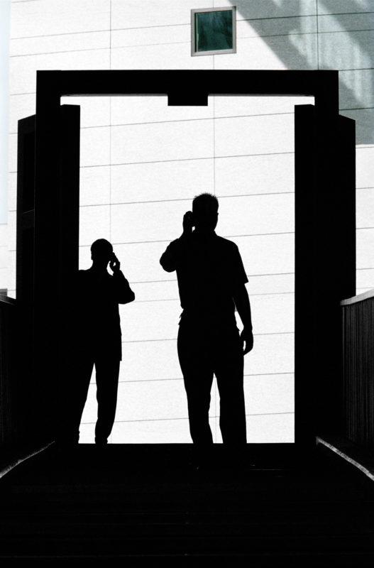 Lifestyle-Fotografie: Zwei Männer telefonieren mobil als Silhouette.