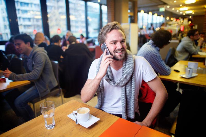 Lifestyle-Fotografie: In einem gut besetzten Café an einer Universität sitzt ein junger Mann an einem der Tische und telefoniert mit seinem Smartphone.