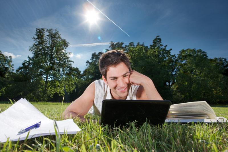Lifestyle-Fotografie: Ein Student arbeitet auf einer Wiese am Netbook online.