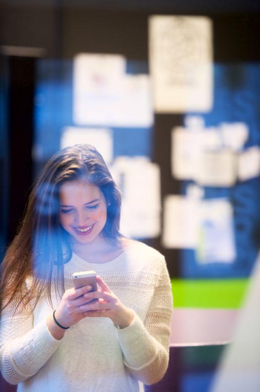Industriefotografie: Lifestyle-Fotografie: Eine Studentin schaut im Universitätsgebäude lachend auf ihr Smartphone.