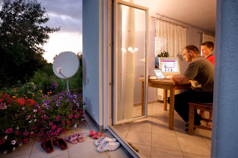Lifestyle-Fotografie: Ein Vater surft gemeinsam mit seinem Sohn abends im Internet. Draußen steht eine Satellitenschüssel.
