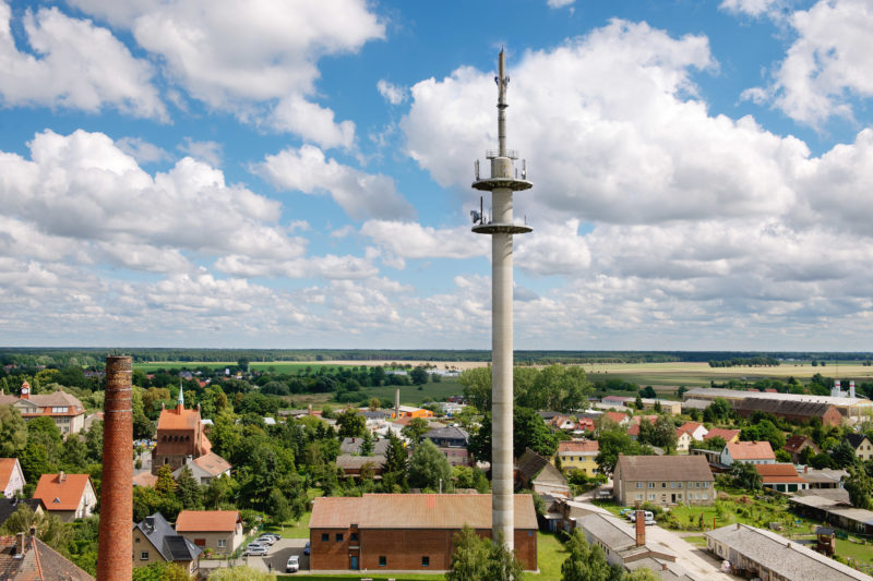 Industriefotografie: Eine LTE-Antenne der Deutschen Telekom AG  in Kyritz mit Technikern bei der Montage.