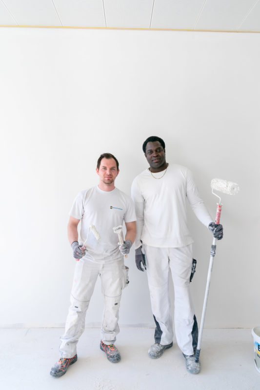 Editorial photography: Employees photography: Two painters on a construction site of a new company building. Both have their tools in their hands, one has white and the other has black skin, both wear white clothes and stand in a white room.