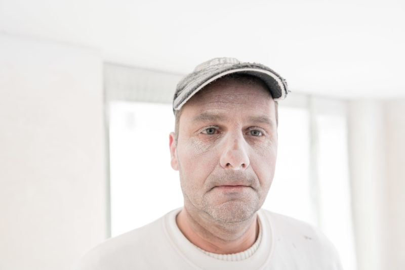 Editorial photography:  A painter sprays the walls with white paint and thereby gets a white face with white eyebrows.