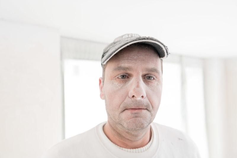 Reportagefotografie: Ein Maler besprüht die Wände mit weisser Farbe und bekommt dadurch ein weisses Gesicht mit weissen Augenbrauen.