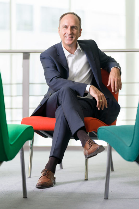 Managerportrait: A manager sits relaxed in an orange designer armchair with his legs laid on top of each other and smiles.  He is illuminated by a flash unit. In the background you can see the bright hall at the entrance of the company.