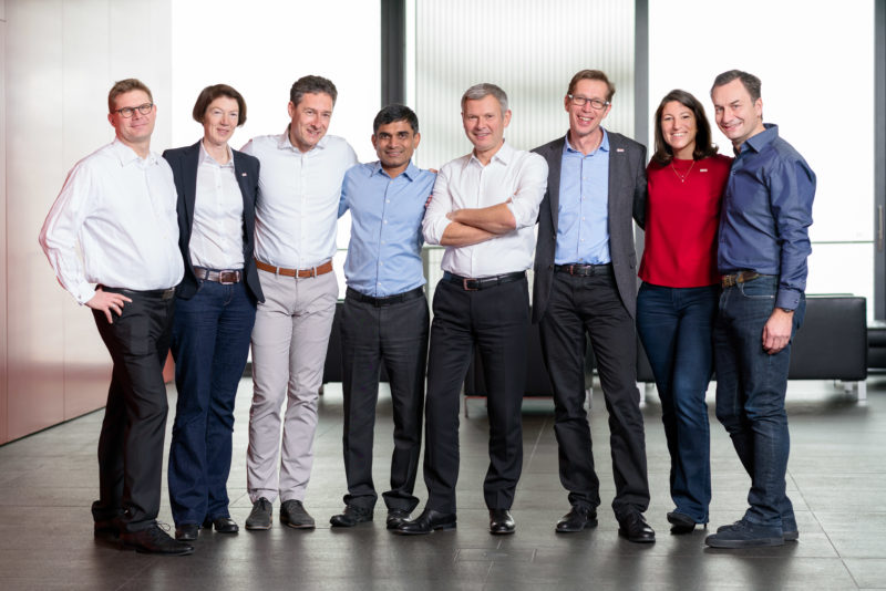 Group photo: Joint full body portrait of executives on the aisle in a company. They deliberately do not wear ties or are even in shirts. The atmosphere is relaxed.