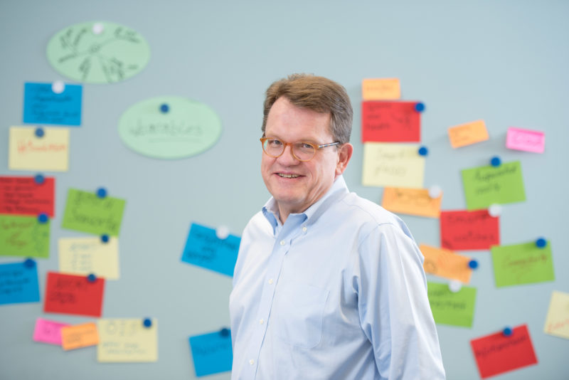 Managerportrait: A manager in a conference room in front of a notice board with many colourfully inscribed notes. He is in his shirt and is not wearing a suit or tie and smiles loosely into the camera. The picture is illuminated with a flash unit. Everything is bright and friendly.