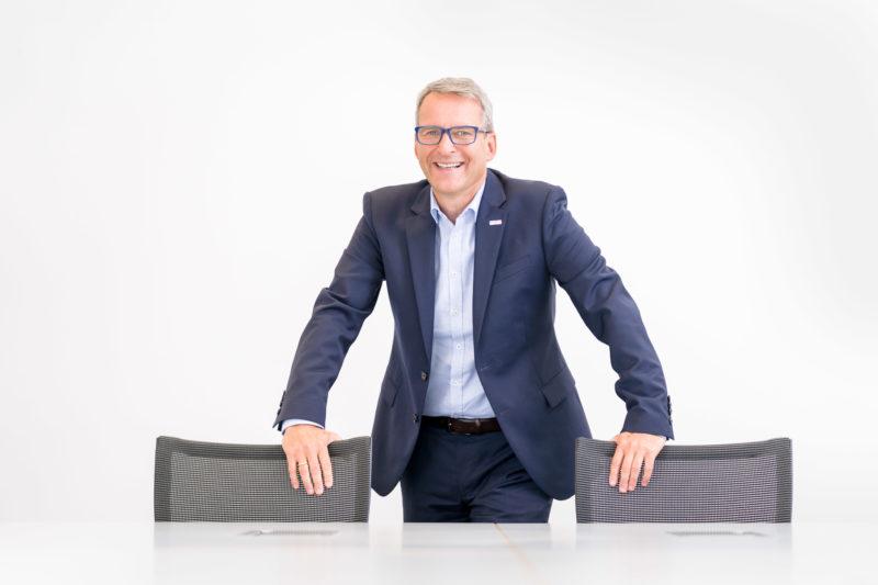 Managerportrait: Ein Manager steht im Konferenzraum seiner Firma an einem großen Tisch mit weisser Tischplatte. Er steht und lehnt sich lässig auf die Stühle am Tisch und lacht.