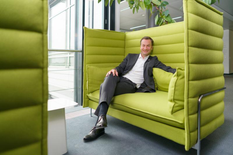 Managerportrait: Ein Manager sitzt bequem in einer Art Sofa, dessen hohe Rückenlehne ihn gegen die Umgebung abschirmt. Im Hintergrund sieht man Pflanzen und ein Fenster. Er trägt Anzug ohne Krawatte. Das natürliche Licht ist zusätzlich mit Blitzlicht aufgehellt.