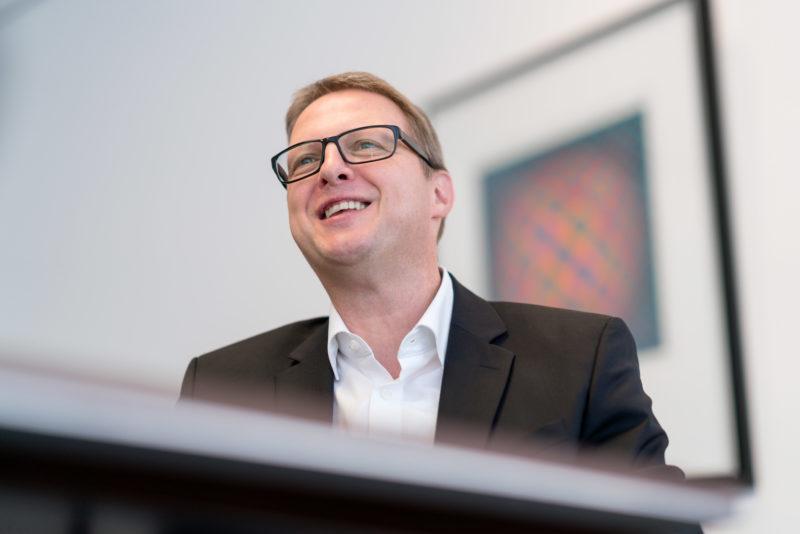Portraitfotografie - Portrait eines Managers einer großen Softwarefirma: Während dem Interview lacht die fotografierte Person offen und entspannt.