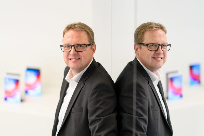 Portraitfotografie - Portrait eines Managers einer großen Softwarefirma: Bei vorhandenem Licht mit offener Blende fotografiert. Die Person spiegelt sich im Glas einer Scheibe.